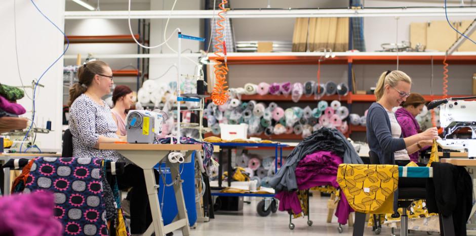 Naisia ompelukoneiden ääressä ompelimon tiloissa.